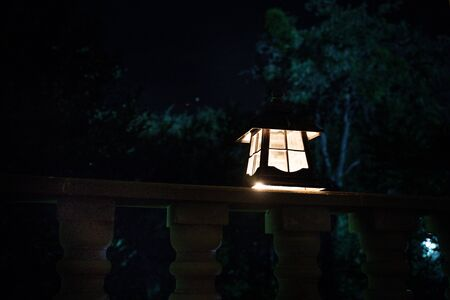 Retro style lantern at night. Beautiful colorful illuminated lamp at the balcony in the garden. Selective focus