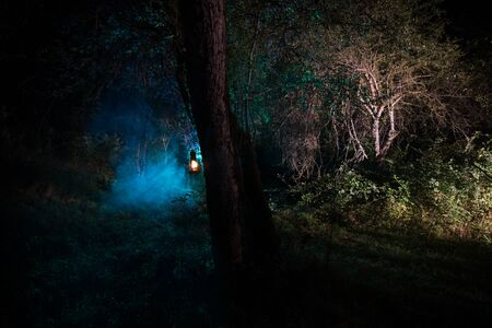 Horror Halloween concept. Burning old oil lamp in forest at night. Night scenery of a nightmare scene. Selective focus. 写真素材