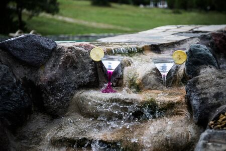 Glass of martini cocktail at mini waterfall with round stones. Selective focus. Season and holidays concept. 写真素材