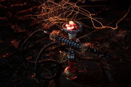 Hookah hot coals on shisha bowl with black background. Stylish oriental shisha at the forest during night time 写真素材