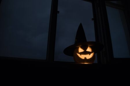 Scary Halloween pumpkin in the mystical house window at night or halloween pumpkin in night on room with blue window. Symbol of halloween in window. Selective focus 写真素材 - 128832021