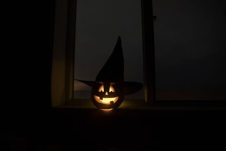 Scary Halloween pumpkin in the mystical house window at night or halloween pumpkin in night on room with blue window. Symbol of halloween in window. Selective focus 写真素材 - 128832024