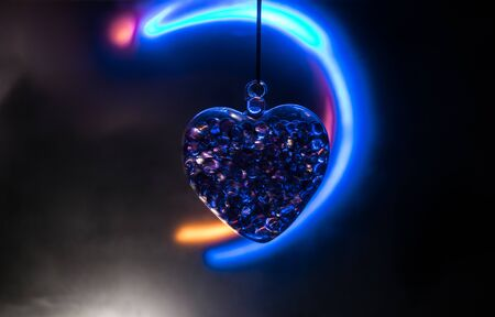 Valentines Day Concept. Beautiful glass heart on dark foggy background. Transparent heart with smoke and glowing lighst on backside. Emptry space for your text