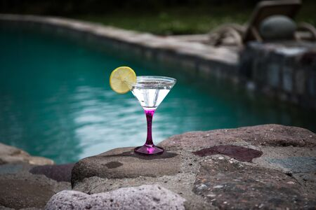 Glass of martini cocktail at swimming pool with forest trees on background. Selective focus. Season and holidays concept. 版權商用圖片