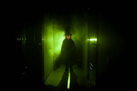 Halloween concept. Creepy silhouette in the dark corridor with pumpkin head. Toned light with fog on background.