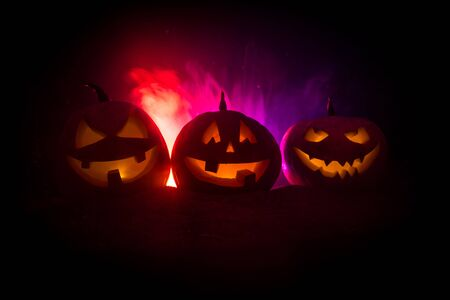 Group of Halloween Jack o Lanterns at night with a rustic dark foggy toned background. Selective focus 写真素材 - 128832071