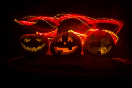 Group of Halloween Jack o Lanterns at night with a rustic dark foggy toned background. Selective focus Stockfoto