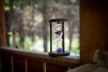 Sand running through the bulbs of an hourglass measuring the passing time in a countdown to a deadline, on a colorful background with copy space. Abstract old sand-glass in forest. Selective focus
