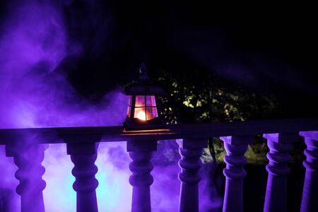 Retro style lantern at night. Beautiful colorful illuminated lamp at the balcony in the garden. Selective focus Imagens - 128832076