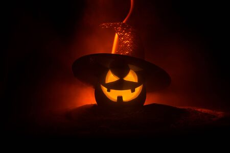 Halloween concept. Jack-o-lantern smile and scary eyes for party night. Close up view of scary pumpkin with witch hat on at dark foggy background. Selective focus. Empty space