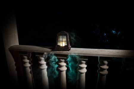 Retro style lantern at night. Beautiful colorful illuminated lamp at the balcony in the garden. Selective focus Imagens - 128832082