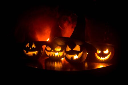 Group of Halloween Jack o Lanterns at night with a rustic dark foggy toned background. Selective focus 写真素材 - 128832086