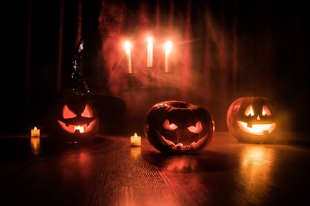 Halloween pumpkin head jack o lantern with glowing candles on background. Pumpkins on wooden floor. Selective focus Stockfoto