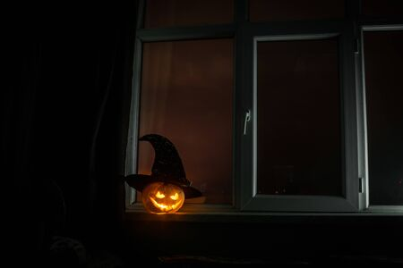 Scary Halloween pumpkin in the mystical house window at night or halloween pumpkin in night on room with blue window. Symbol of halloween in window. Selective focus 写真素材 - 128832175