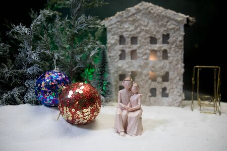 Toy artwork decoration. Happy New Year Celebration, Young Family standing in the Front Yard in snow with trees and small dollhouse. Selective focus Stockfoto