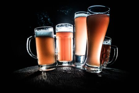 Creative concept. Beer glasses on wooden table at dark toned foggy background. Selective focus