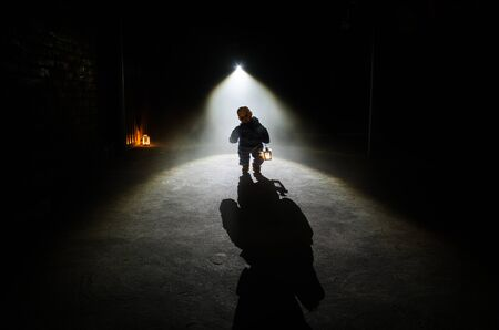 Horror scene of a scary childrens ghost, Silhouette of scary baby doll on dark foggy background with light. Horror Halloween concept