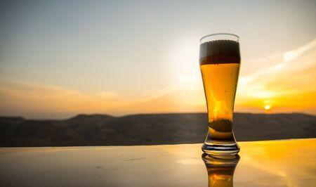 Glas Bier am Strand bei Sonnenuntergang. Kühlkonzept für Sommergetränke. Nahaufnahme eines Glases Bier vom Fass mit dem Bokeh des Sonnenlichts Hintergrund, Weichzeichner