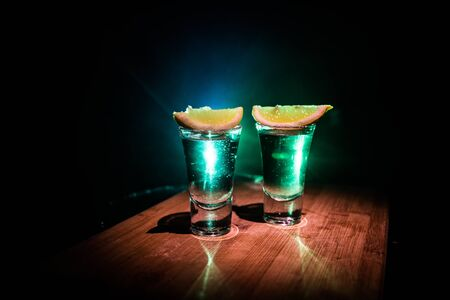 Club drink concept. Tasty alcohol drink cocktail tequila with lime and salt on vibrant dark background or glasses with tequila at a bar. Selective focus