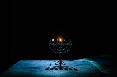Low key image of jewish holiday Hanukkah background with menorah (traditional candelabra) on dark toned foggy background Banco de Imagens