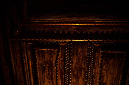 Close up view of old antique wooden door inside a dark room. Selective focus. Horror concept