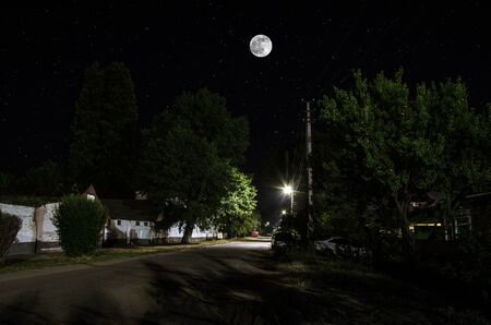 Full moon over quite village at night. Beautiful night landscape of old town street with lights Reklamní fotografie - 128832594