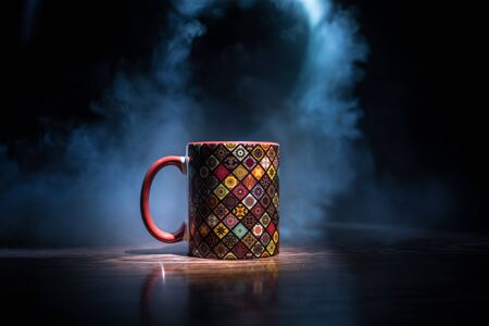 Beautiful eastern style textured ceramic cup of coffee (or tea) with smoke over dark toned background. Close up view. Stok Fotoğraf