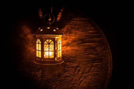 Arabic lantern with candle at night for Islamic holiday. Muslim holy month Ramadan. The end of Eid and Happy New Year. Copy space on dark background. Stockfoto