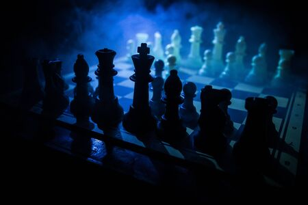 Chess board game concept of business ideas and competition. Chess figures on a dark background with smoke and fog. Selective focus 写真素材 - 128907550
