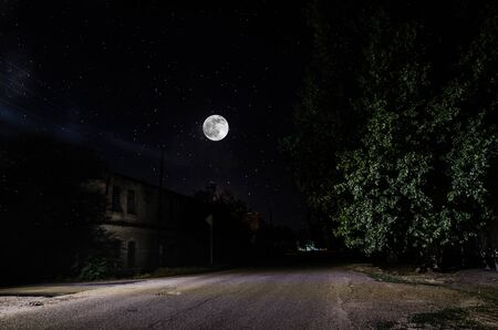 Full moon over quite village at night. Beautiful night landscape of old town street with lights