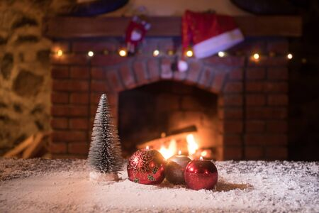 Christmas Room Interior Design, Closeup view of Christmas decorations on table with snow and fireplace on background. Empty space for your text. Selective focus