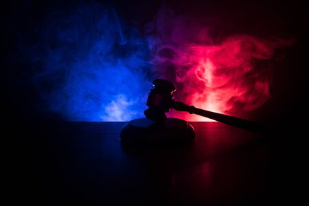 Law theme, mallet of the judge on wooden desk with Lady Justice Statue. Law gavel on dark foggy background with light. Selective focus 写真素材