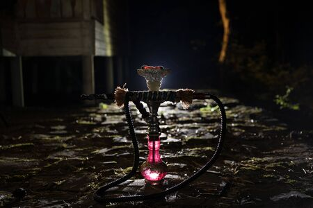 Hookah hot coals on shisha bowl with black background. Stylish oriental shisha at the forest during night time Banco de Imagens