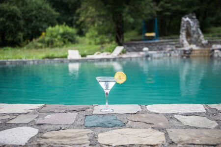 Glass of martini cocktail at swimming pool with forest trees on background. Selective focus. Season and holidays concept. 스톡 콘텐츠