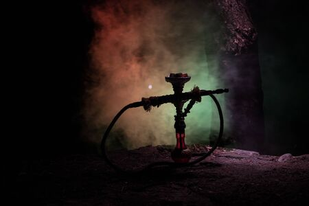 Hookah hot coals on shisha bowl with black background. Stylish oriental shisha at the forest during night time Фото со стока
