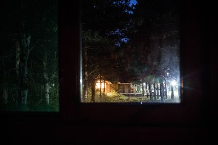 House in the forest at night. View from window. Selective focus. Long exposure shot Banco de Imagens