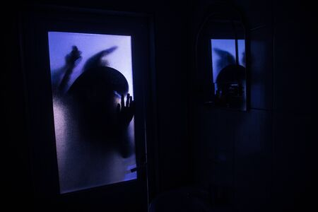 Horror silhouette of woman in window. Scary halloween concept Blurred silhouette of witch in bathroom 写真素材