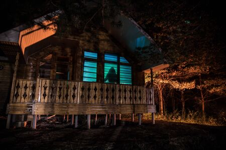 Old house with a Ghost in the forest at night. Horror silhouette at the window. Old building in forest. Surreal lights. Horror Halloween concept