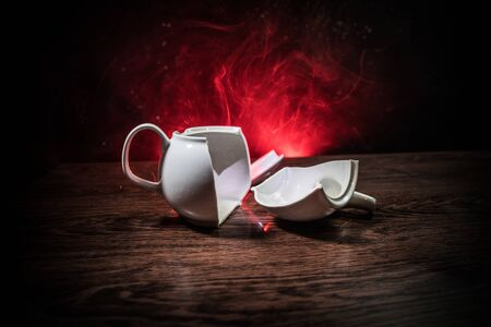 broken teapot on a dark toned foggy background. Pieces of ceramic teapot on wooden table. Selective focus 写真素材 - 129422777