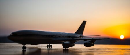 Artwork decoration. White passenger plane ready to taking off from airport runway. Silhouette of Aircraft during sunset time. Selective focus