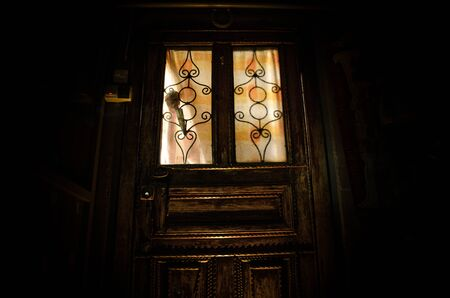 Silhouette of an unknown shadow figure on a old wooden door through a closed glass door. The silhouette of a human in front of a window at night. Scary scene halloween concept 写真素材 - 129422811