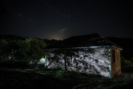 Mountain night landscape of building at forest at night with moon or vintage country house at night with clouds and stars. Summer night. Photo taken with long exposure 写真素材