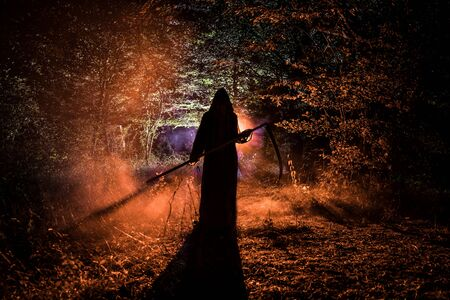 Death with a scythe in the dark misty forest. Woman horror ghost holding reaper in forest, halloween concept 写真素材