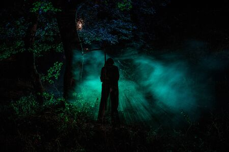 Death with a scythe in the dark misty forest. Woman horror ghost holding reaper in forest, halloween concept Stock Photo