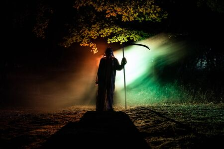 Death with a scythe in the dark misty forest. Woman horror ghost holding reaper in forest, halloween concept