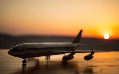 Decoración de obras de arte. Avión de pasajeros blanco listo para despegar de la pista del aeropuerto. Silueta de aviones durante el atardecer. Enfoque selectivo