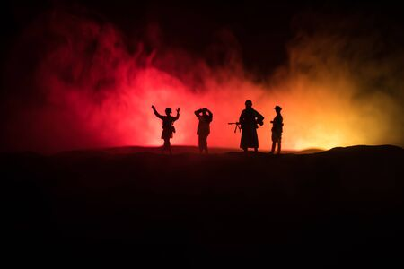 Battle scene. Military silhouettes fighting scene on war fog sky background. A German soldiers raised arms to surrender. Plastic toy soldiers with guns taking prisoner the enemy soldier. Artwork Stock Photo