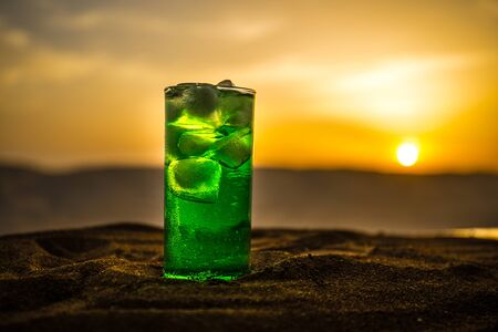 Close up wet glass of green cold mint drink, colorful orange sunset background on the terrace. Cooling summer drink. Summer fresh and cooling inspiration, evening contrast color combination. Relax.