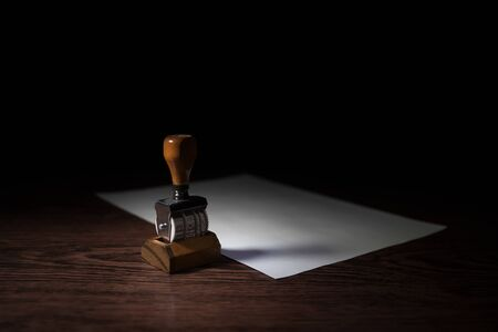 Close up view of rubber date stamper on wooden table with dark toned foggy background. Selective focus