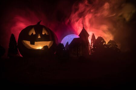Horror view of Halloween pumpkin with scary smiling face. Head jack lantern with haunted building and tree on dark toned foggy background. Zdjęcie Seryjne